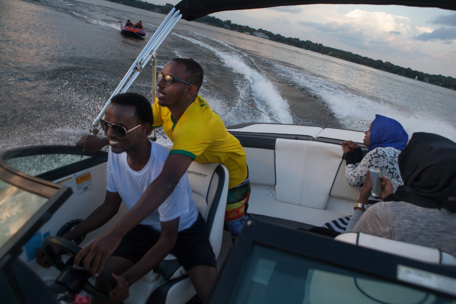 On a summer afternoon with his friends, Abdikadir Hassan (far left) and Somali friends who are visiting from Columbus, Ohio and Kitchener, Canada go water tubing on White Bear Lake, one of the many lakes around Minneapolis.