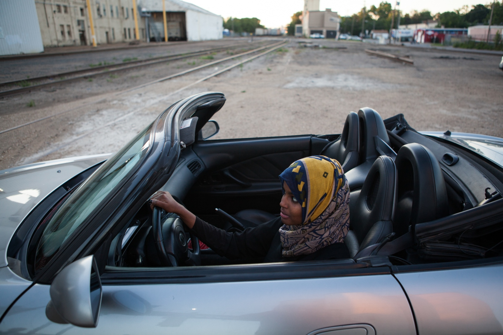Fartun Mahamoud Abdi looks at herself in the mirror of her friend's convertible. Ms. Abdi sits on the controversial Countering Violent Extremism committee, which is a government-backed initiative meant to keep youth away from both radicalization and street crime through after-school outreach programs.