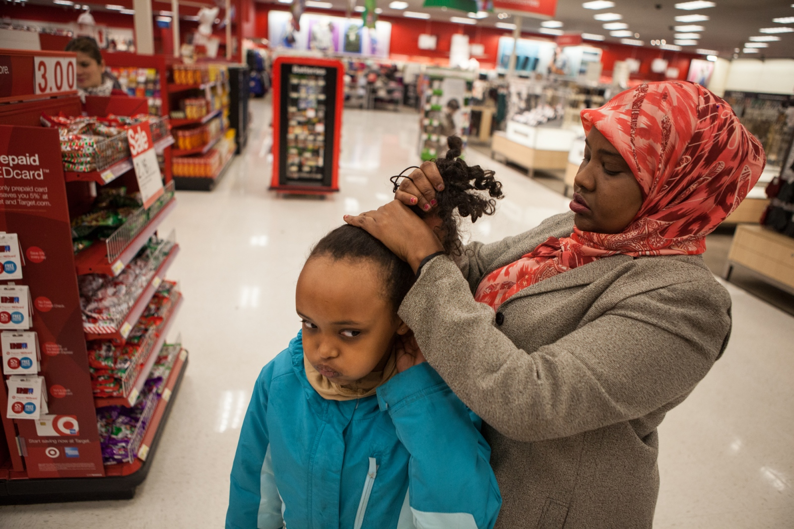 Saciido Shaie fixes her daughter's hair at a Target in Minneapolis. Ms. Shaie says she and her husband never asked the children to wear a hijab, but that normally they insist on doing so themselves.