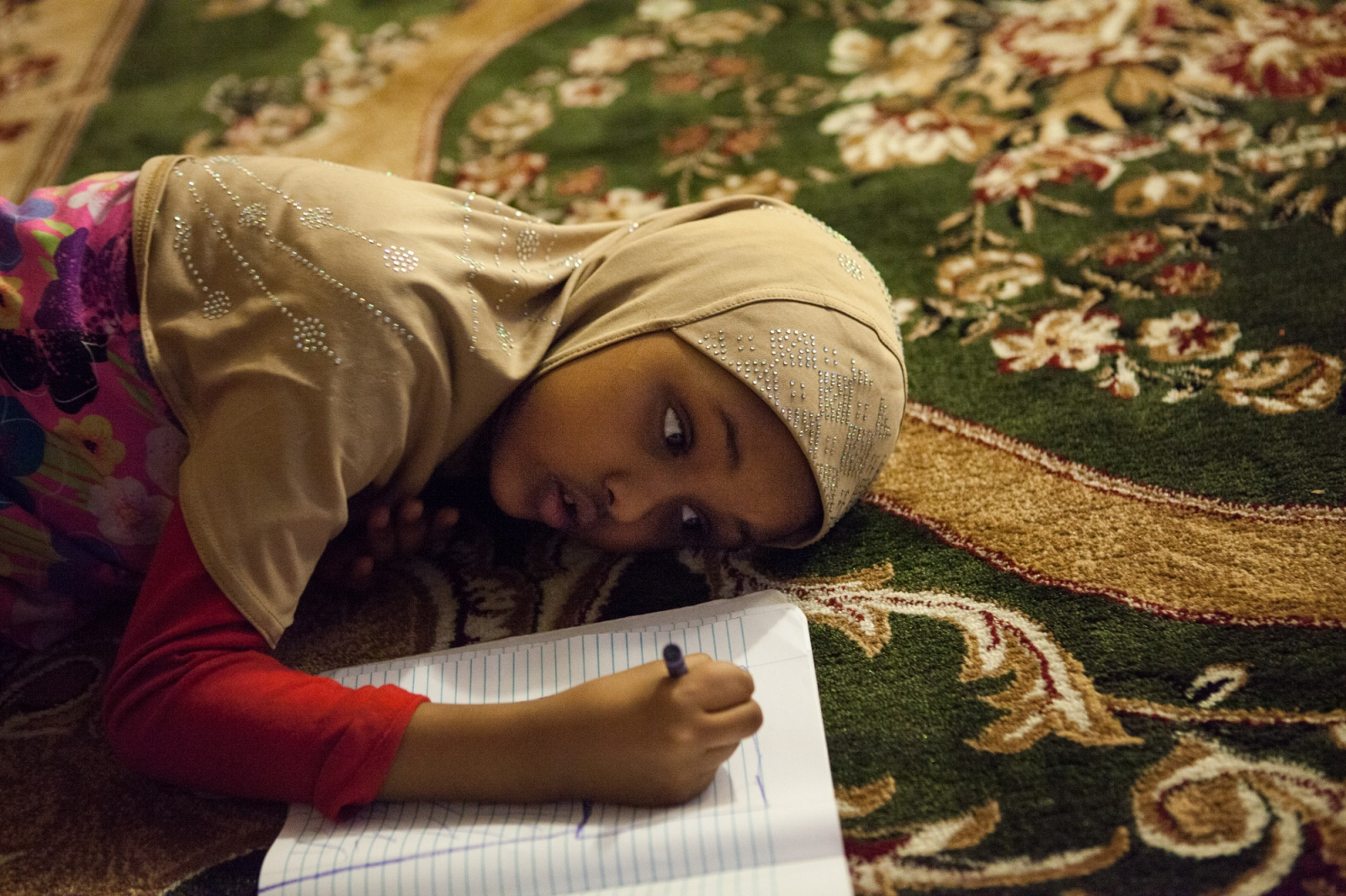 Amal draws pictures in her coloring book on the floor of her home in Minneapolis.