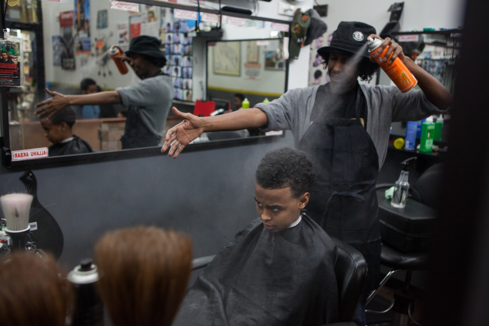 Jamaal Farah cuts the hair of a Somali boy at his barber shop in Karamel Mall. Mr. Farah is also a popular comedian and social media star among the Somali diaspora.