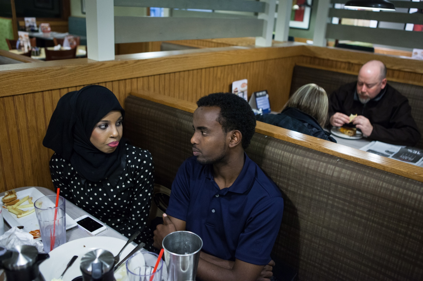 Abdikadir Hassan sits with his friend, Sabah Hassan, at a diner in Minneapolis, where they argued about whether it was OK for the white mayor of the city to wear a hijab to a Somali event.