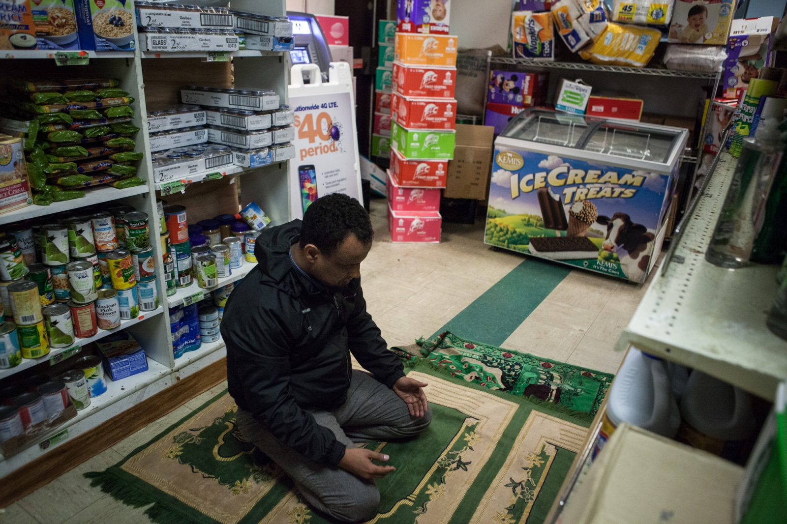 Haji Yusuf, 37, performs an afternoon prayer in an isle of the Mogadishu Mall market in St. Cloud, MN. The small city, located about 65 miles northwest of the Twin Cities, has been attractive to Somalis primarily because of job opportunities at local manufacturing and meat packing plants.