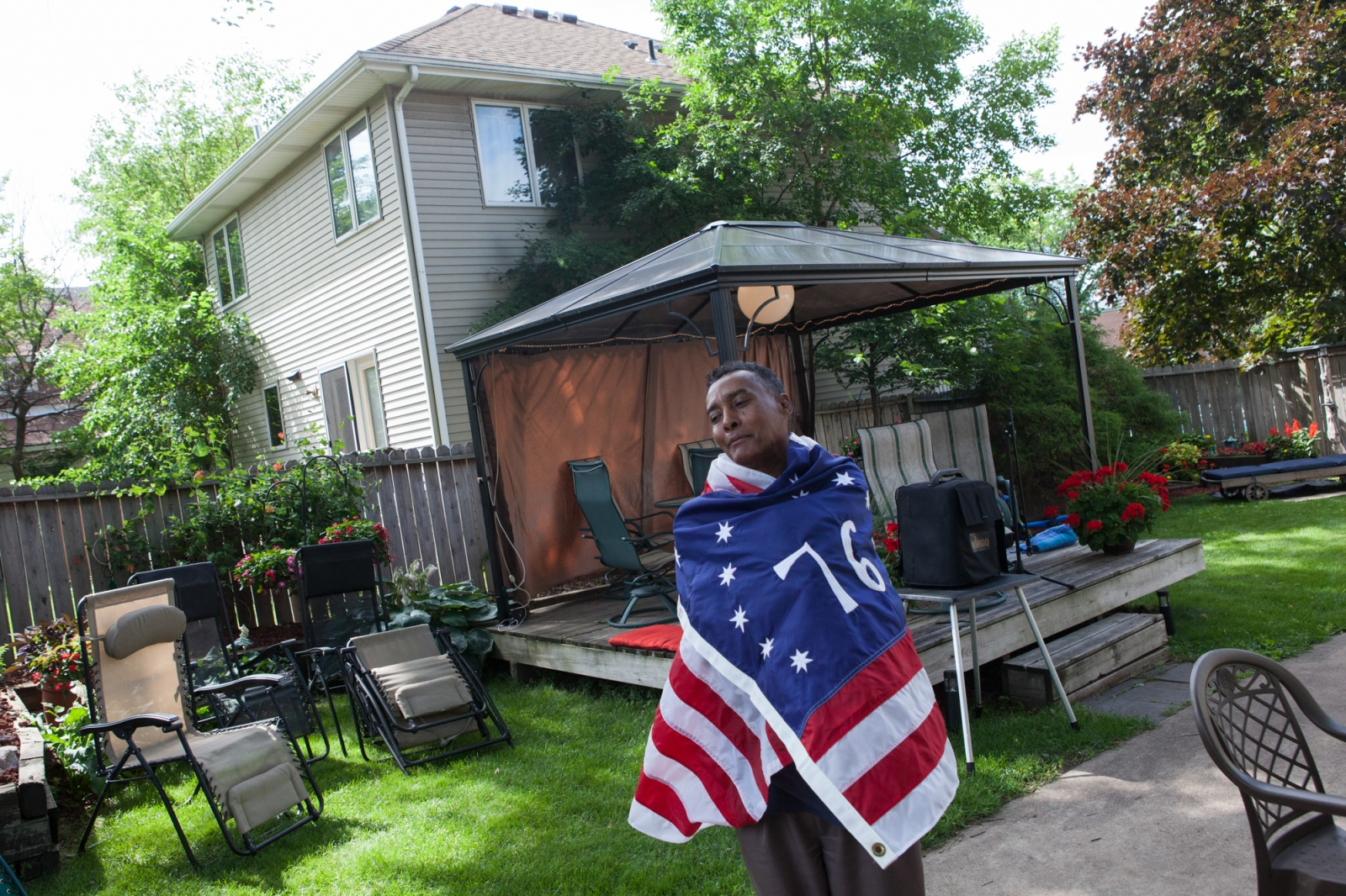 Osman Omar, who says he will run for president of Somalia for the second time in 2016, wraps himself in an American flag while taking a break from helping to prepare for a community Iftar dinner.