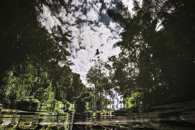 A sky reflection of the forest in a hot water pool