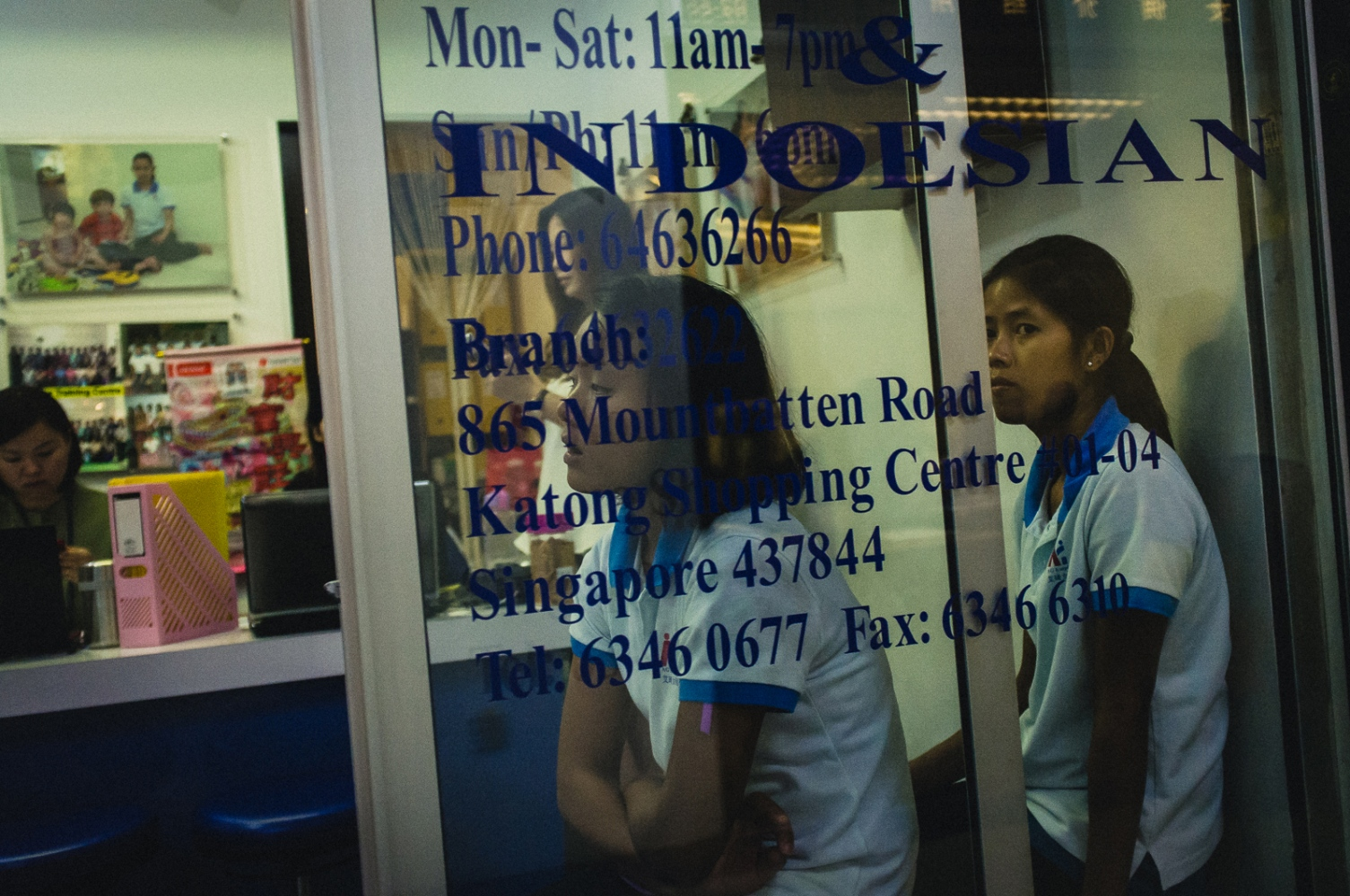 Women seeking employment as foreign domestic workers in Singapore seen through the window of a 'Maid Agency' in a shopping centre in Singapore. While agencies are occasionally able to offer help and support to foreign domestic workers, exploitative practices are not uncommon, and the Singapore governemnt has been criticised for not not being proactive enough in enforcing regulations and legislation relating to the industry.