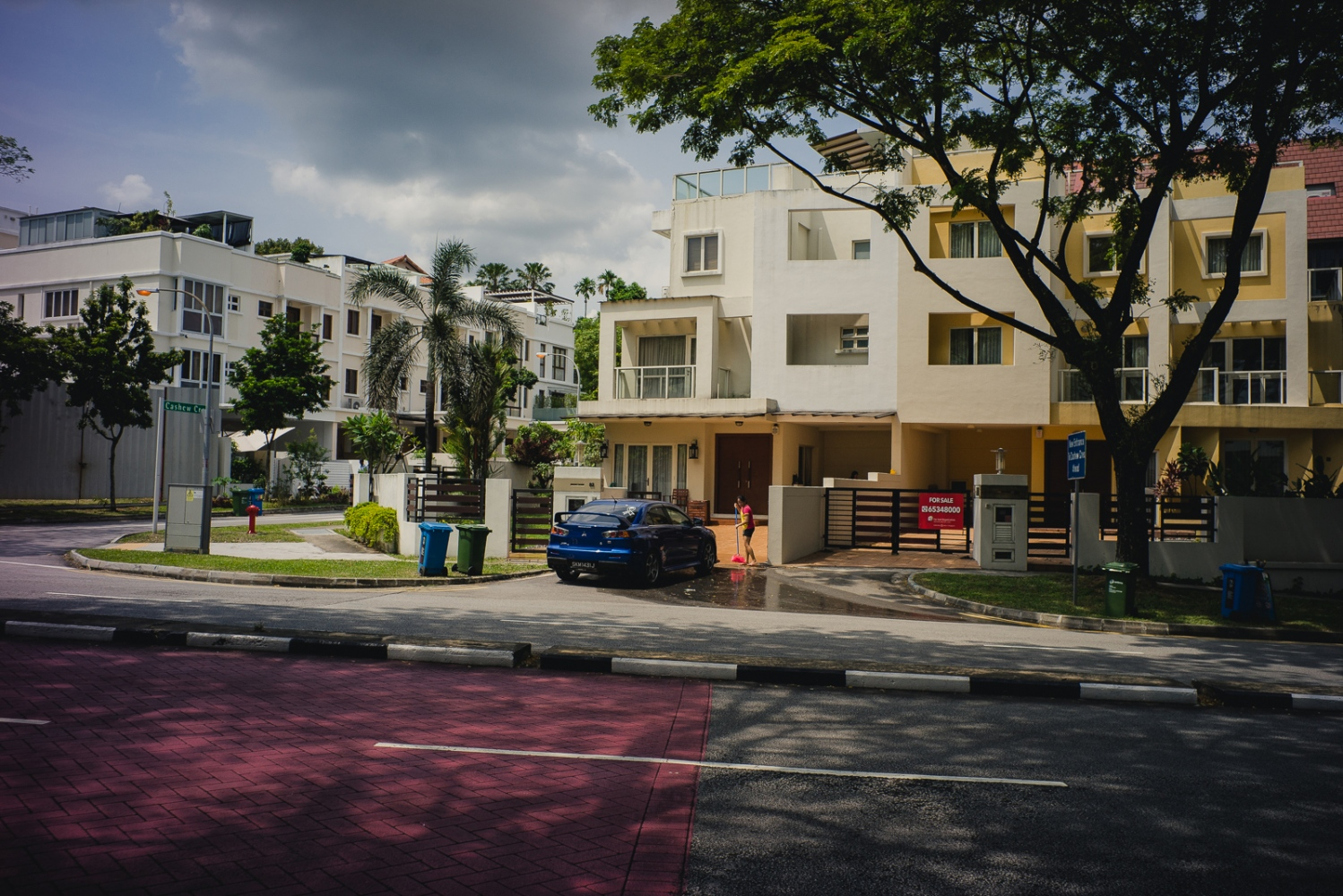 A Foreign Domestic Worker sweeps the driveway after washing a car outside a landed property in Singapore. Foreign domestic workers are required by Singapore law to live with their employers.