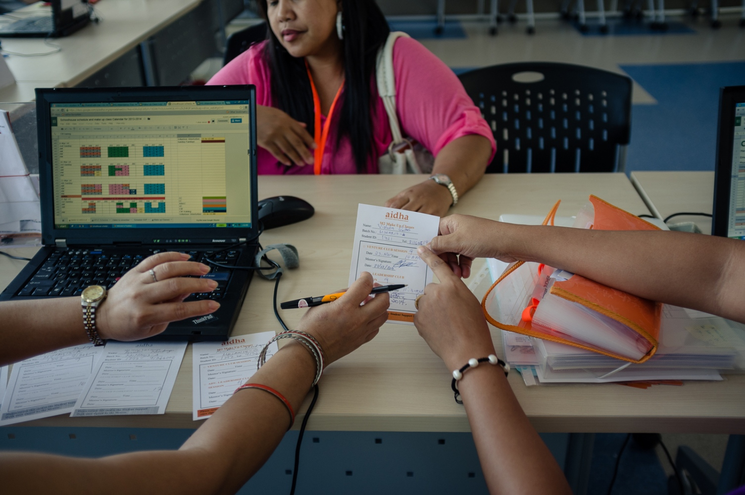 Foreign domestic workers in a school classroom which serves as a temporary office for 'Aidha' - a business school for domestic workers in Singapore.