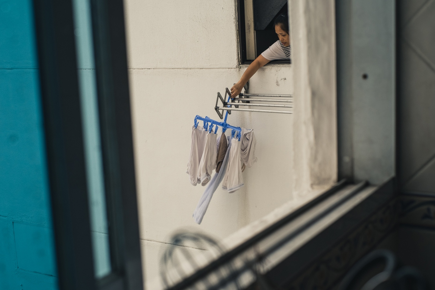 A Foreign domestic worker hangs washing from the window of a condo in Singapore. Foreign domestic workers are required by Singapore law to live with their employers.