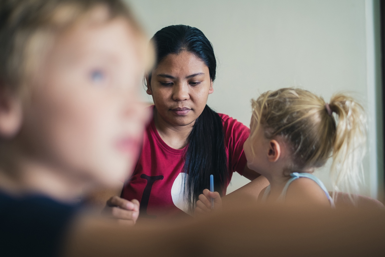 Foreign Domestic Worker Ghie (Marifel Mosquera) draws and plays games with the two children she looks after for her employer. Marifel, like all domestic workers, lives with her employer.