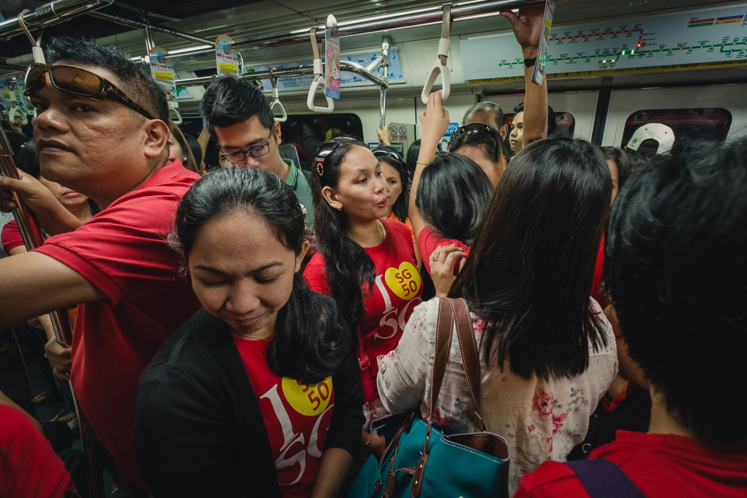A group of foreign domestic workers wearing 'SG50 I love Singapore' t-shirts mingle with Singaporeans on the MRT public transport system in Singapore,
