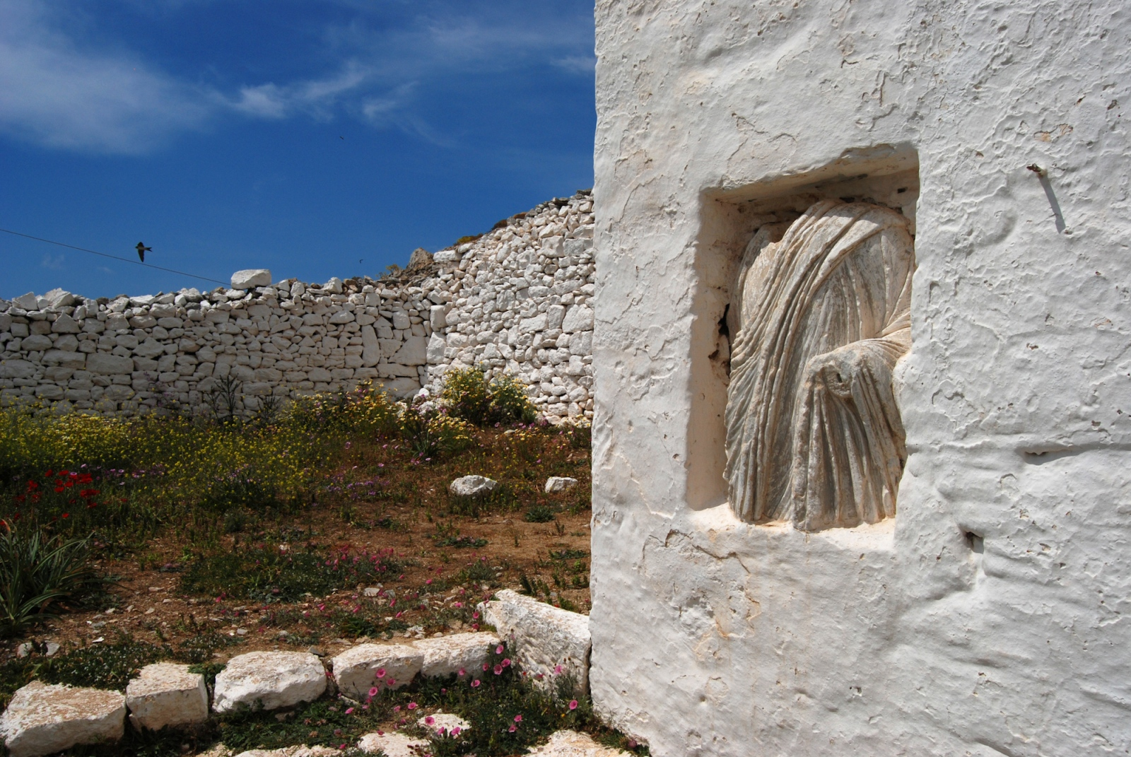 Church bell tower with embedded ancient torso. Folegandros island, Greece.
