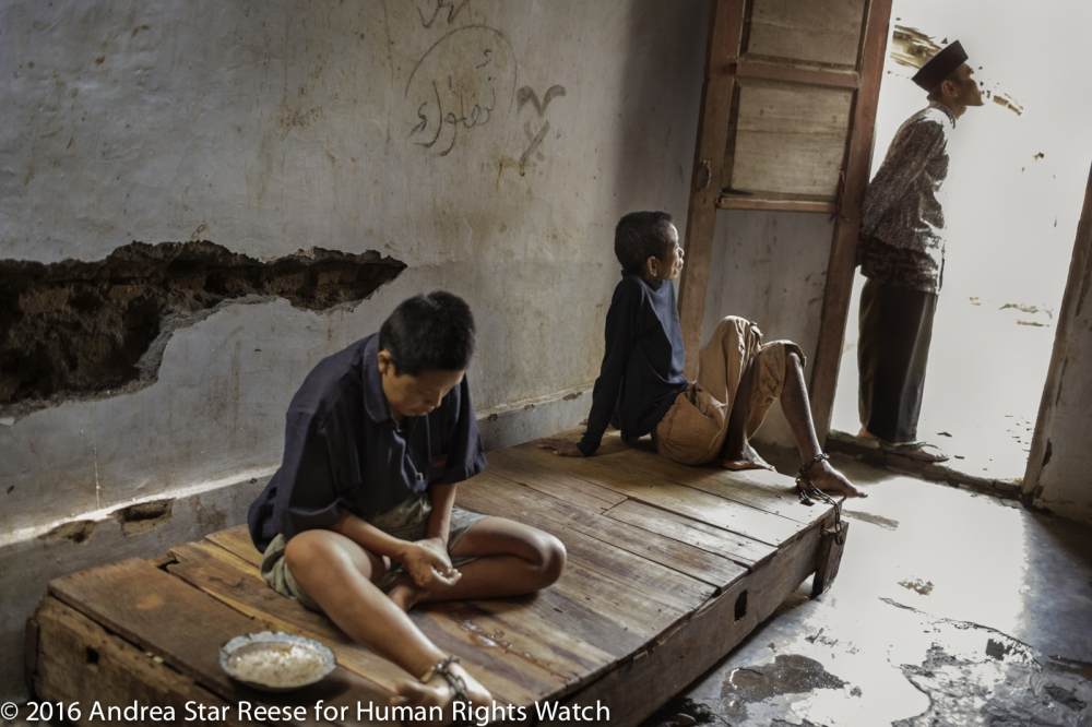 "Two residents at the Bina Lestari healing center in Brebes, Central Java, are confined to a wooden platform bed while an Islamic faith healer stands nearby. At the center, all residents are chained and receive traditional ""healing"" through prayer, consumption of special drinks, or blessings with holy water."