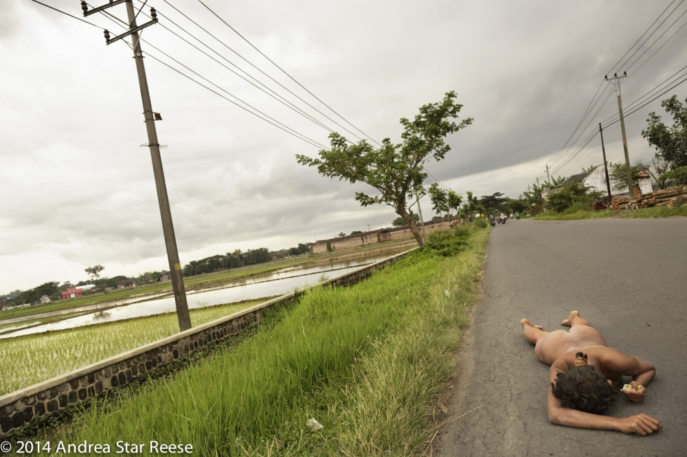 A woman lies on a road distraught and confused near Klaten, Central Java. Just before this moment a man living nearby threw a rock at her to discourage her from staying in the area. The woman does not know where she is or how to find her home. Homeless men and women with psychosocial disabilities are common in Indonesia, and are at high risk for assault, malnutrition and rape.