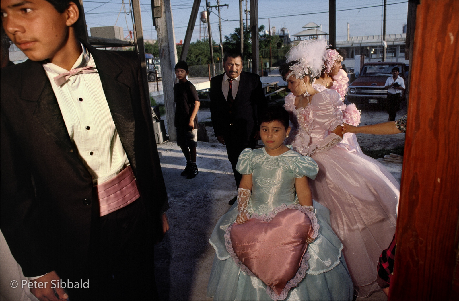 In Matamoros, a quinceañera or coming out ceremony is held in an Avenida Uniones church across from a chemical plant, whose noxious fumes assault pariticipants arriving at the cermony. © Peter Sibbald, 1993