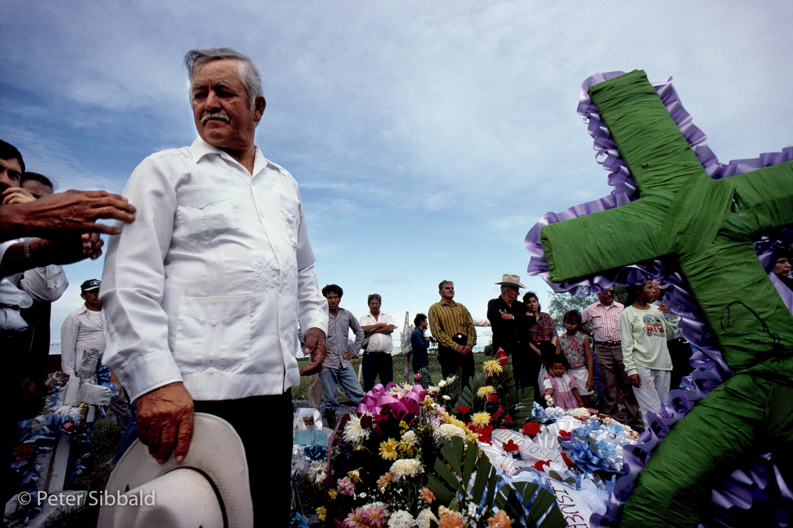 A man bids farewell at a funeral for his farmer brother on the outskirts of Matamoros. Most of the land along the Rio Grande was traditionally farmed. Nowadays, farming is being discouraged and even when land is not outright expropriated as in the case of Las Rusias, often it falls into the hands of industrialists when old farmers die. The fate of this farm remains uncertain. © Peter Sibbald, 1993
