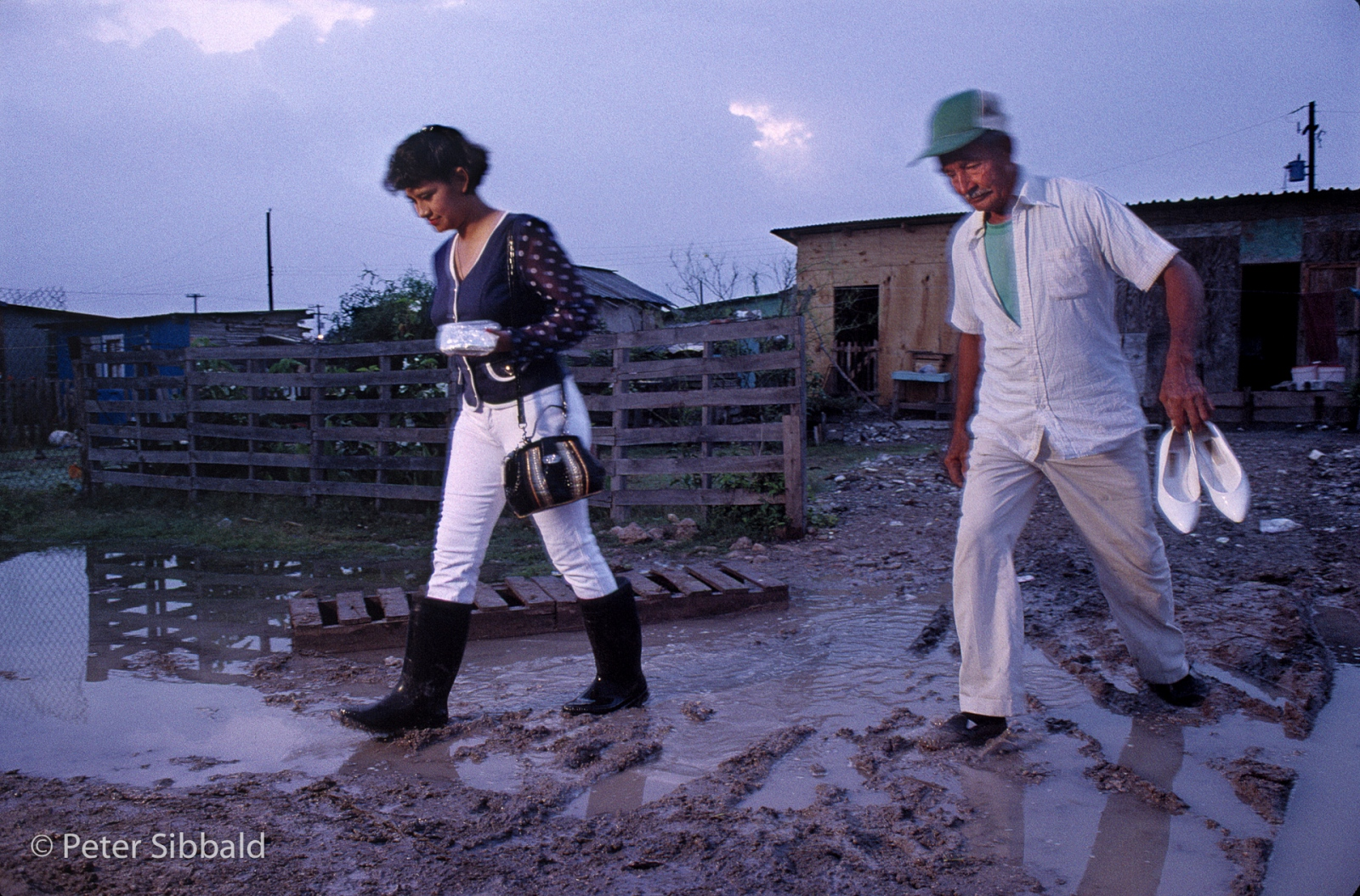 At dawn, Beti's grandfather Jesus Garcia escorts her through the colonia's ubiquitous mud to the bus-stop where he will trade her clean pumps for her rubber boots. © Peter Sibbald, 1993