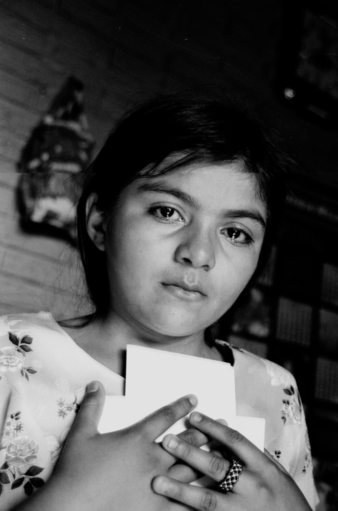 Carla Herrera, 11, clutches pictures of her mother, Carmen Climaco. Climaco was given 30 years for an abortion that was ruled a homicide. 2006