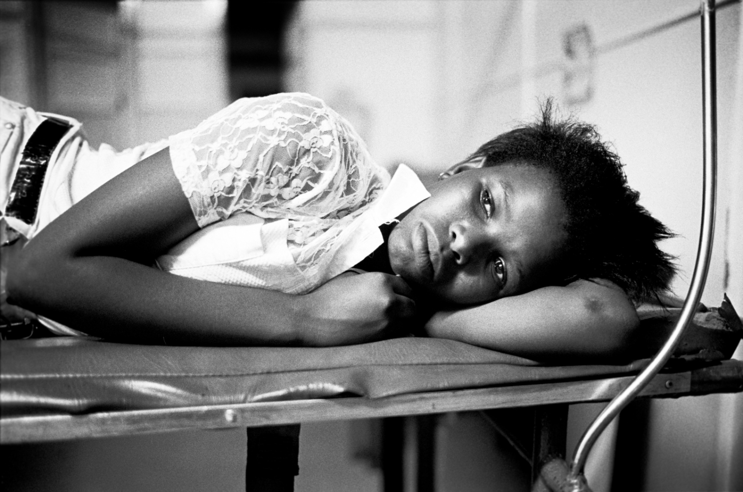 A young girl rests at a hospital, after being rescued from a suicide attempt prompted by her rape. 1998