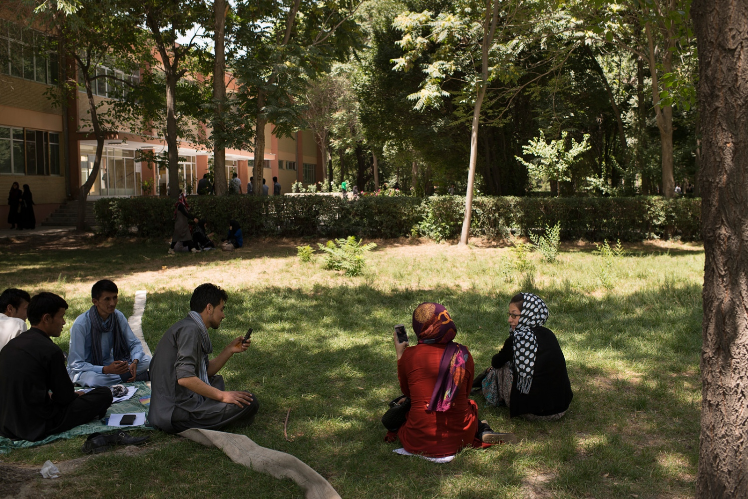 KABUL, AFGHANISTAN | 2014-08-09 | A mix group of students socialize in between exams as they sit together inside Kabul university campus. While social media is allowing the youth to socialize and keep in touch without having to go through the family, it still an odd seen to see a mix group sit together, even on liberal campus of Kabul university.