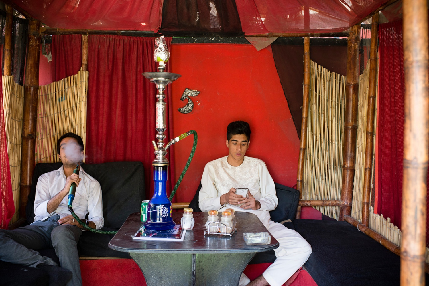 KABUL, AFGHANISTAN | 2014-08-10 | Young Afghan men, all in their early 20s, socialize and smoke hooka at Cafe Che, in Western Kabul. Cafe Che is one of the fewer cafes that have become very popular among young people in mixed groups as a meeting place.