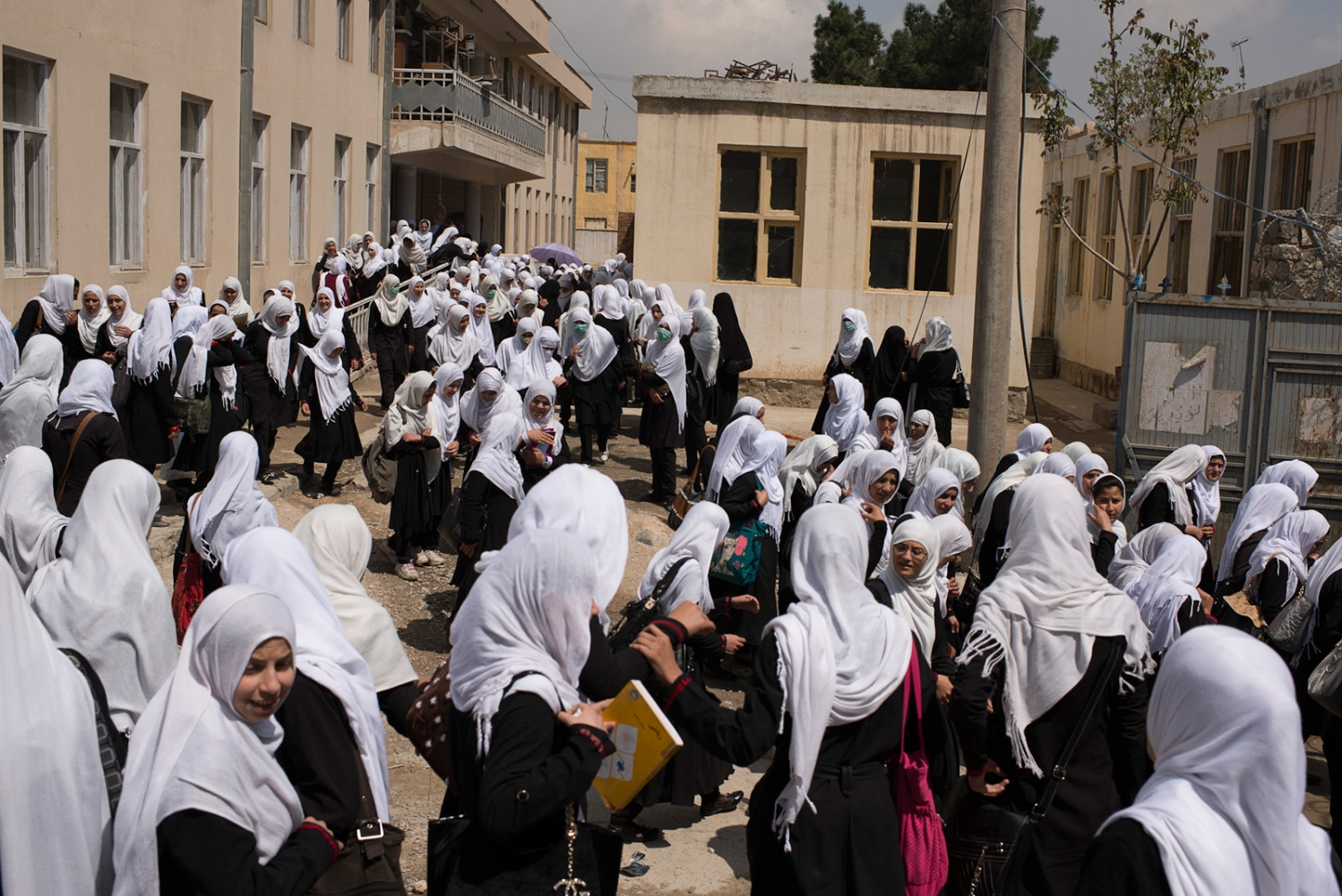 KABUL, AFGHANISTAN | 2015-04-20 | Students attending the second shift of Nur Muhammad Shah all-girl school pour into the hallways on a Monday morning. This shool, located on the hill (Sar-e Tappa) in Karte Now neighborhood, admits 13,000 girls over 5 shifts from grade 1 to 12. Under Taliban regime, girls were not allowed to attend schools. Now, 14 years later, thousands and thousands of girls in black uniform and white headscarves, passionately walk to their schools everyday here in Kabul.