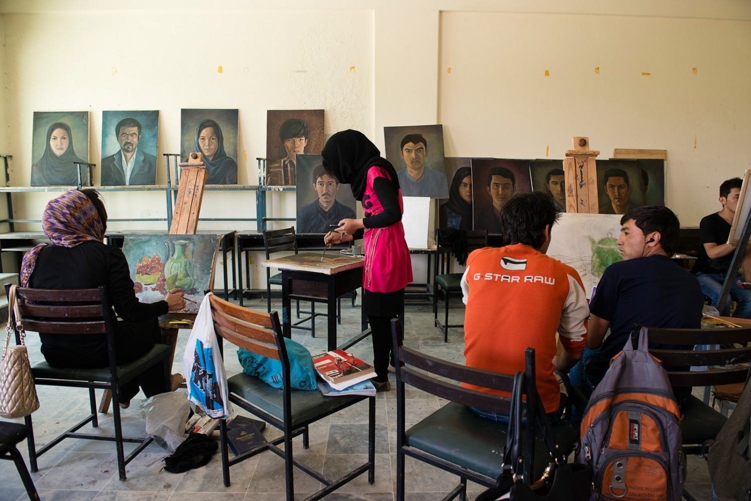 KABUL, AFGHANISTAN | 2015-06-13 | A group of students work on their projects inside a painting class at Kabul University Faculty of Fine Arts.