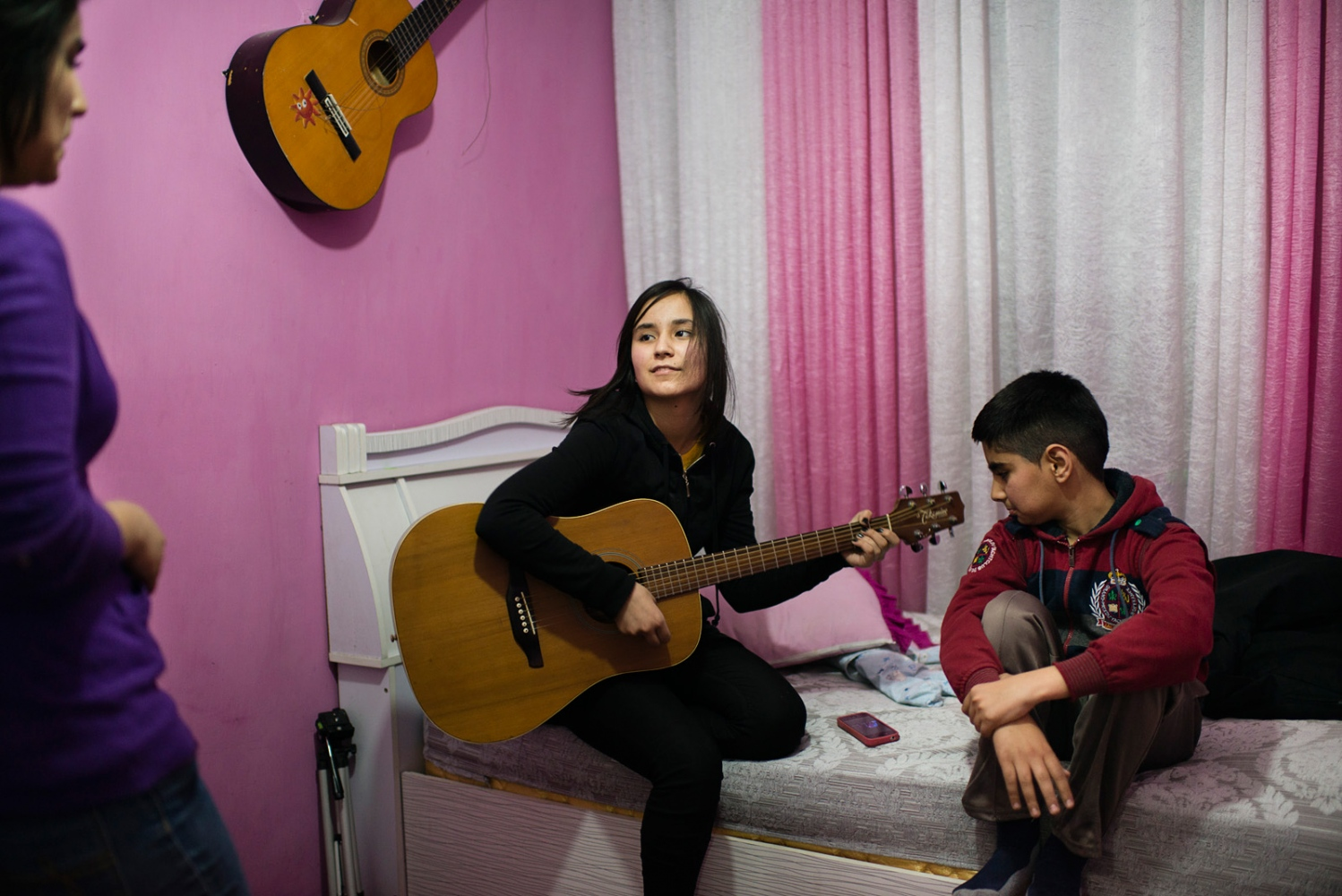 KABUL, AFGHANISTAN | 2015-01-06 | Zhala (16) plays a cover of Avril Lavigne's song in her room while her younger brother and older sister sing along.