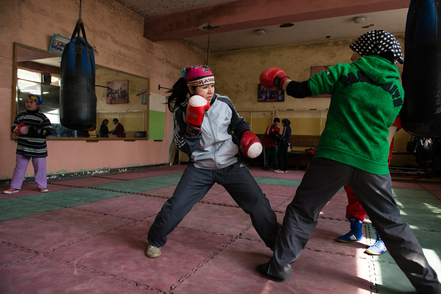 KABUL, AFGHANISTAN | 2015-02-28 | Members of afghan girls national boxing team practice and exercise weekly with their male coach, Mr Sharifi, at Olympic Stadium in Kabul. Most of them believe that boxing has given them confidence and independence in their personal life as well.