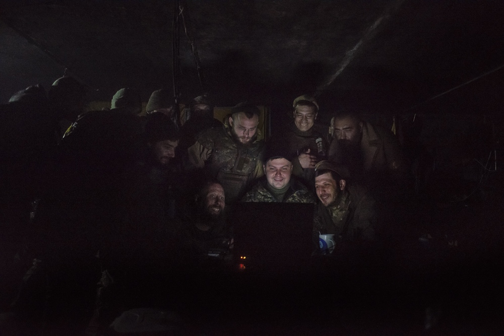 The men watch reconissance footage of an enemy troops being hit by a shell after crossing into Ukrainian held territory.