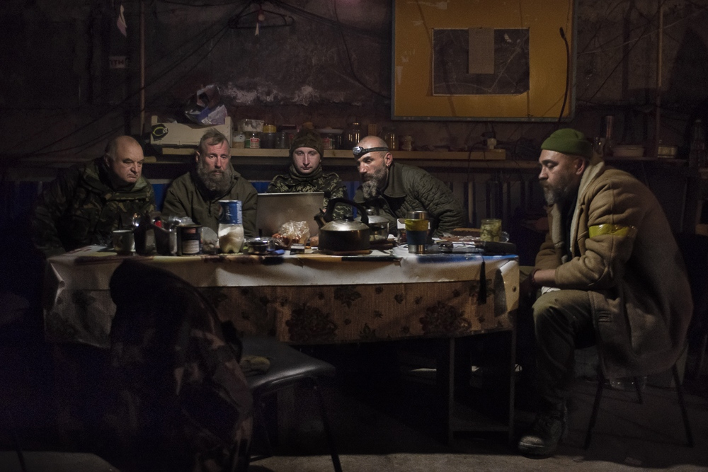Despite the shelling continuing outside, Commander, Newt, Martin, Pilot, and Santa whatch a documentary about the battle for Donetsk airport, which they had particpated in last year, in a bunker on the frontline in Avdiivka, a hundred meters from DNR troop positions.