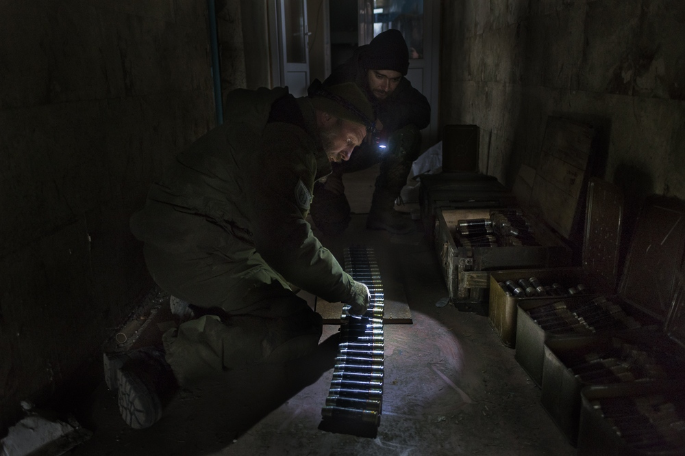 Ivan, a regualr army soldier holds the light for Newt, an unpaid volunteer soldier in Right Sector as he prepares an ammunition belt for their postion's guns.