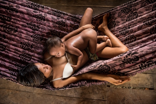 Zeneide de Castro Barbosa, 16, breastfeeds her daughter Ariane Barbosa de Souza, 23 months, in a hammock of her home in the indigenous community of Piranhas, Amazonas, Brazil on the Igapo Acu river June 3, 2015. Doctors and dentists working with the  Basic Health Unit River (BFHU) system, provide primary care visiting indigenous communities via the   Igaracu, a boat outfitted and designed to provide medical and dental assistance. They v isit these communities during a 20 day period up and down parts of the Amazon river and its tributaries. The Igaracu is the first government subsidized medical boat for Brazil.