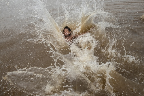 A young boy jumps back first into the river while going after a soccer ball while he and others paly in the Divino Espiroto Santo Community on the Rio Madeirinha, a tributary of the Amazon river in Amazonas Brazil Wednesday June 18, 2015. Doctors and dentists working with the  Basic Health Unit River (BFHU) system, provide primary care visiting indigenous communities via the   Igaracu, a boat outfitted and designed to provide medical and dental assistance. They v isit these communities during a 20 day period up and down parts of the Amazon river and its tributaries. The Igaracu is the first government subsidized medical boat for Brazil.