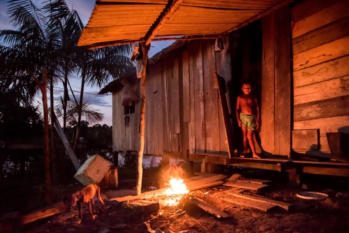 Lit by a fire, a young girl stands in the doorway of her home in the Terra Preta Community in Brazil Monday June 22, 2015. Doctors and dentists working with the  Basic Health Unit River (BFHU) system, provide primary care visiting indigenous communities via the   Igaracu, a boat outfitted and designed to provide medical and dental assistance. They v isit these communities during a 20 day period up and down parts of the Amazon river and its tributaries. The Igaracu is the first government subsidized medical boat for Brazil.