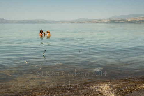 A woman plays with her dog in the Sea of Galilee April, 24, 2014 in the Golan Heights, Israel. Photo Ken Cedeno