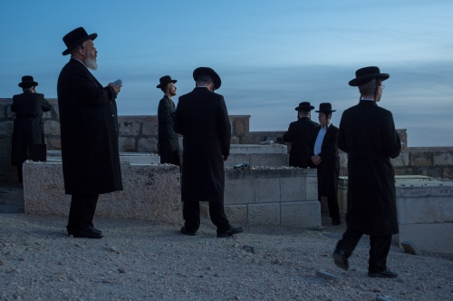Ultra-orthodox Jews pray at sunset in the old cemetery looking over the Old City of Jerusalem April 22, 2014. Ken Cedeno