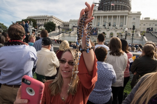 A woman takes a selfie as she holds a handful of rosaries on the West Lawn of the US Capitol as Pope Francis, 78, speaks to the crowds follwing his first address to U.S. Congress in the House Chamber of the U.S. Capitol September 24, 2015 in Washington, DC. Pope Francis is the first pope to address a joint meeting of Congress and will wrap up his visit here befroe heading to New York City