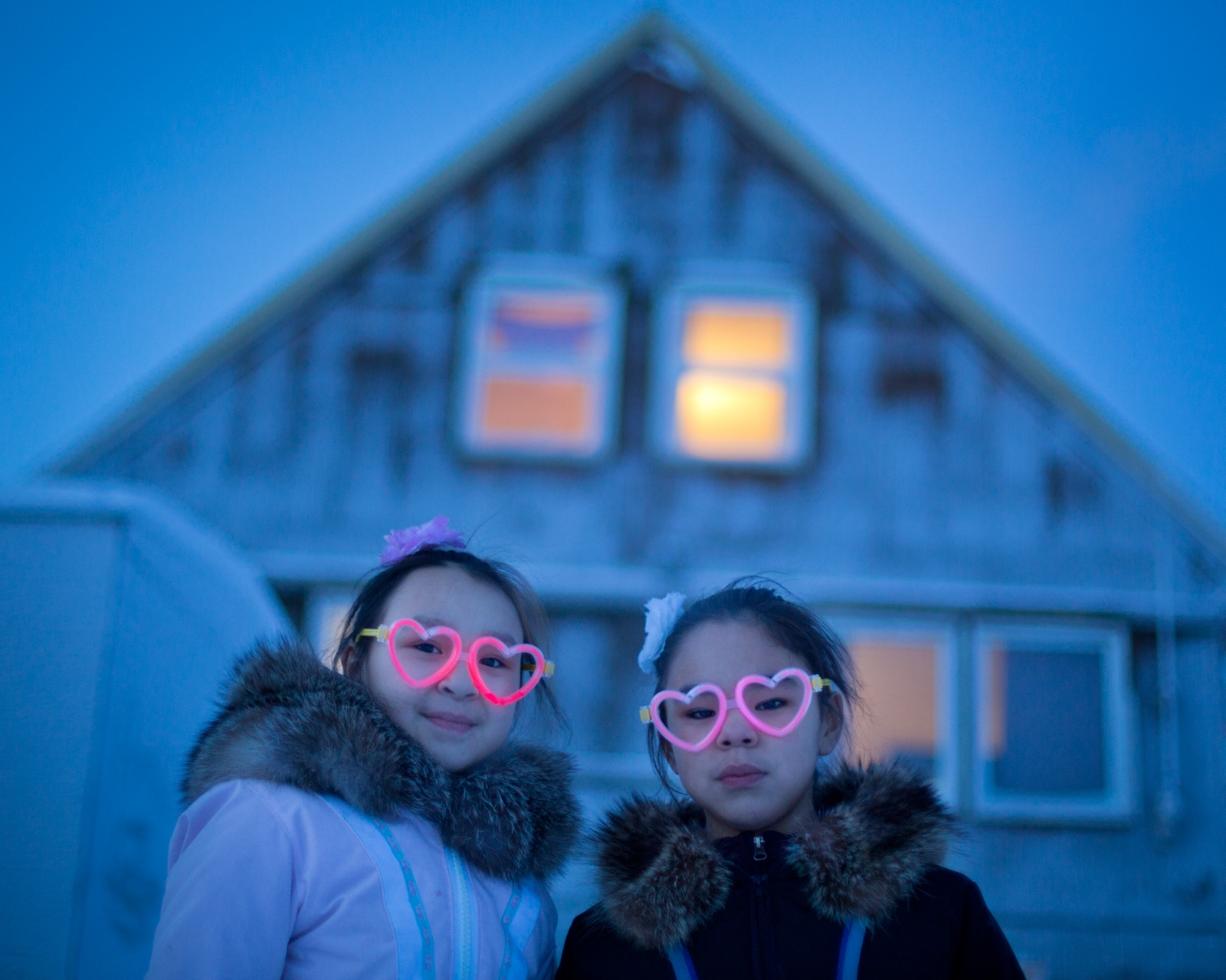 Joy and Amelia, 10, don heart-shaped glasses for Arctic Bay's weekly Friday Night Dance. Through a long and dark winter, frequent community events such as dances, sports games, sewing clubs, and church services make for plenty of social opportunities all winter long.