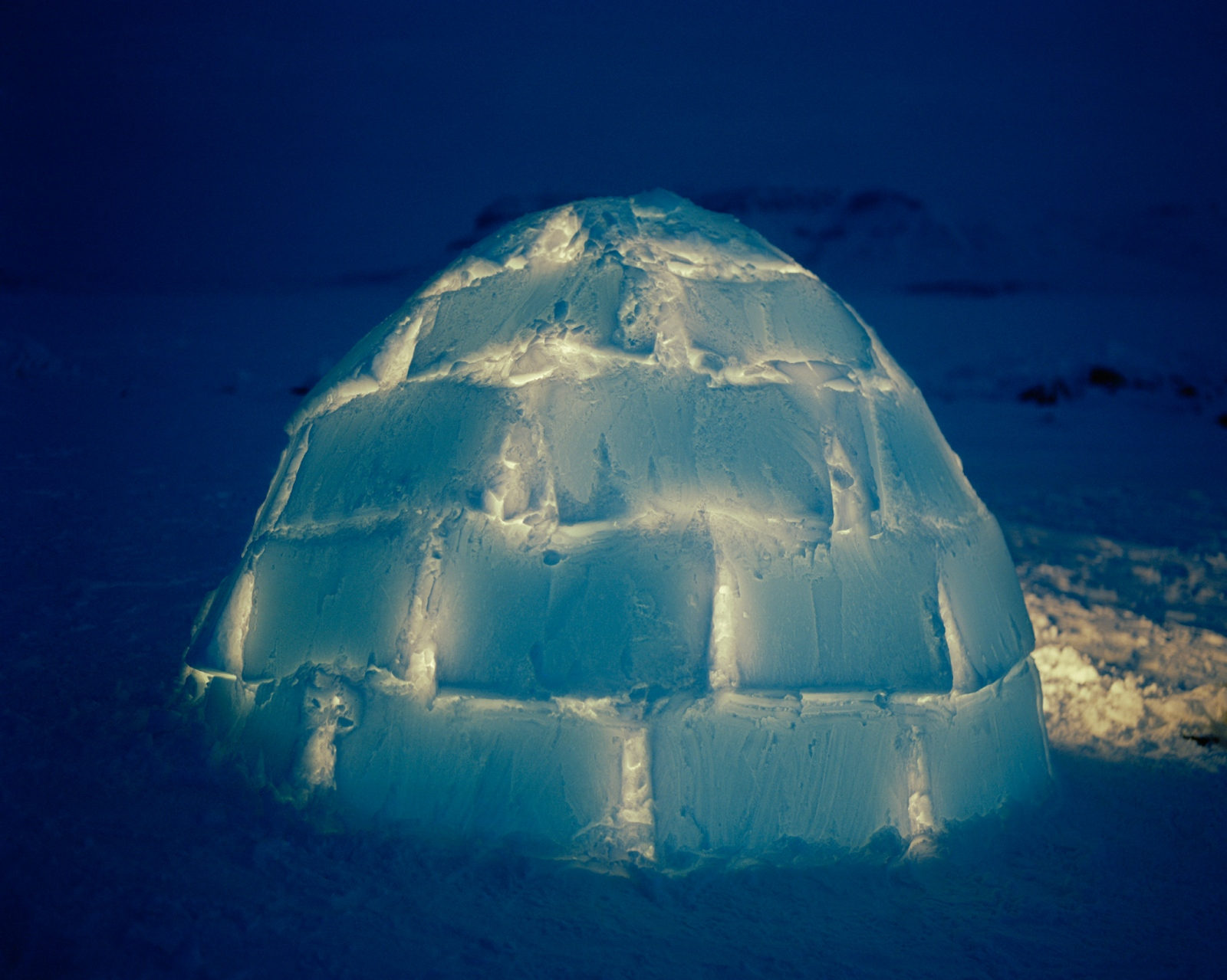 An iglu glows through the afternoon on the darkest day of the year. Jack Willie, a photographer in Arctic Bay, asked his uncle to help him build one, using blocks of wind-packed snow cut with a snow knife. While no longer frequently used, many Inuit know how to build iglus for survival shelters, should bad weather conditions arise when hunting out on the land.