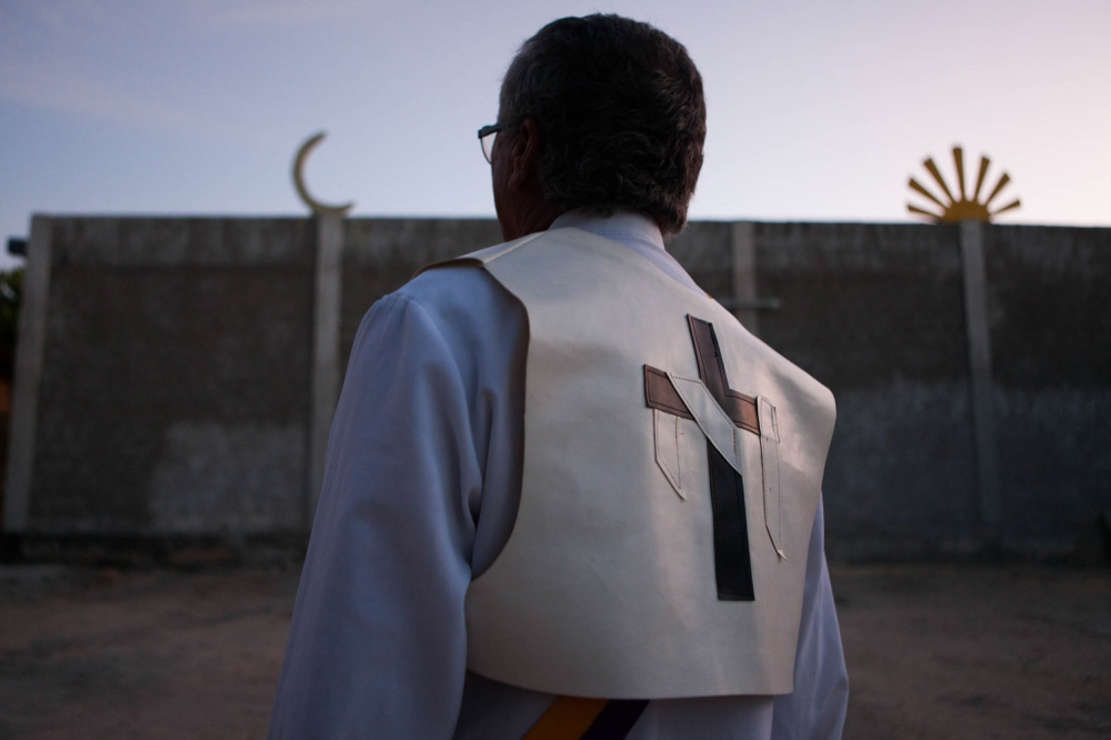 · Edon stands outside the temple as the sun goes down. He wears the outfit which symbolises that he is able incorporate spirits, as he is a medium with a capacity to serve as a channel. Cavalcante do Goais, 2015.  // · Edon en el patio en el atardecer. Usa la vestimenta que simboliza que es capaz de incorporar a los espiritus como un canal de comunicación.  Cavalcante do Goais, 2015.