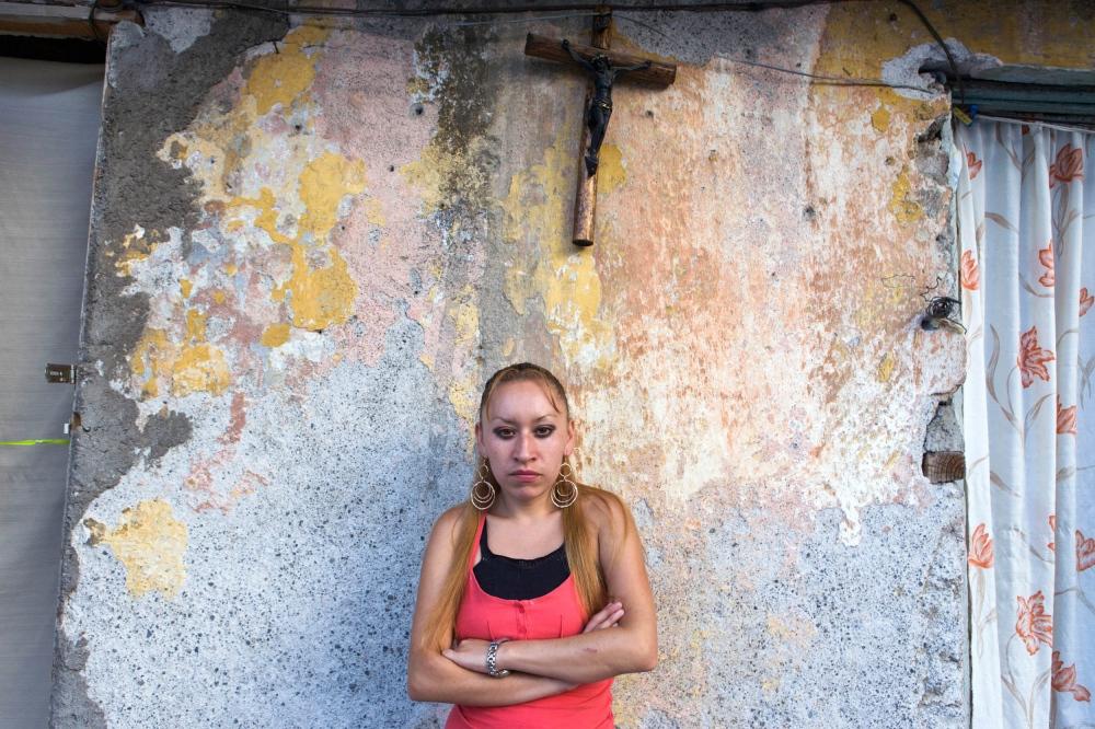· Maria Luisa in front of one of the rooftop rooms that comprises her family´s home. Daugther of Blanca, she is one of the seven adults that shared one side of the rooftop. July 7th, 2008 // · María Luisa frente a su casa en la azotea. La familia de Eleazar compartía cinco cuartos de un metro cuadrado, incluyendo baño y cocina, entre los diez familiares que comprendían tres generaciones.7 de julio de 2009