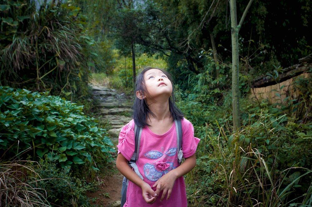The young daughter of the Huang Family, Huang Junyan, takes a break during her daily trek up the mountain to her home from school. The Huang family lives in YingPanXu, a rural mountain town in the eastern Jiangxi Province on the border with Hunnan Province.
