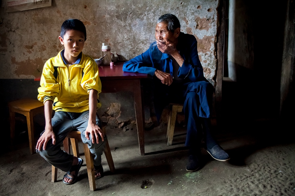 Two days before the patriarch, Huang Jingming, died, he relaxes and smokes a cigarette as his grandson, Huang Juntao, sits nearby. After Huang Juntao's mother, Lai Zhilan, ran away, his father, Huang Fuan, sent him to live with his relatives while he worked as a woodcutter in the neighboring Hunnan Province.