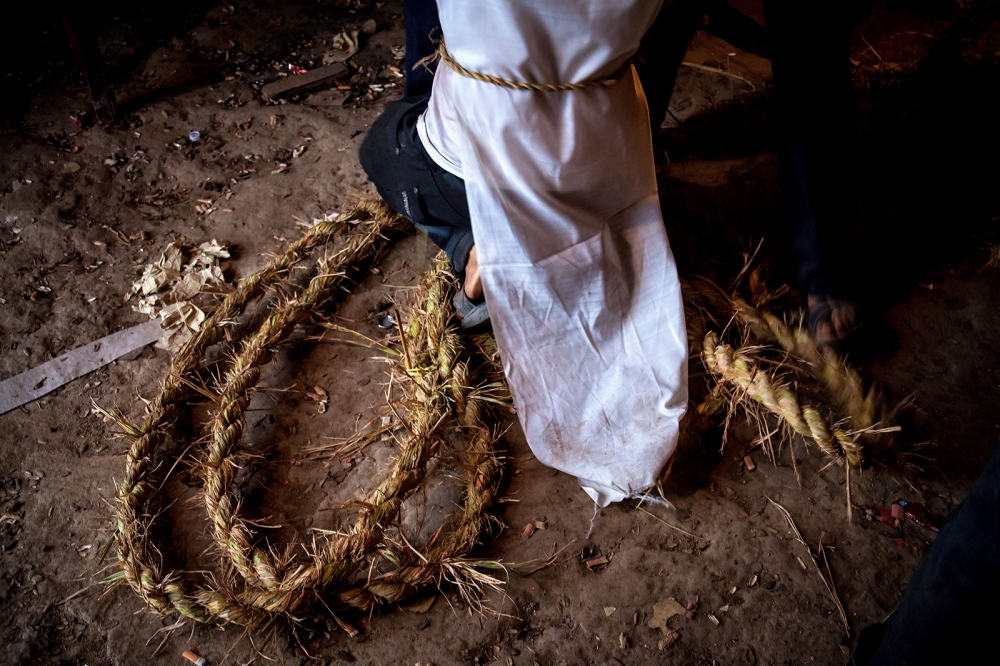 A Huang family member kneels amongst the hand woven rope that will be used to carry Huang Fuan to his grave.