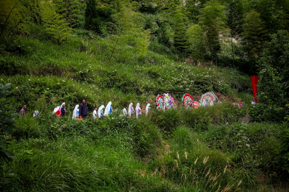 The funeral procession walks up the hill to the burial site. The family wears ceremonial headdresses to show they are in mourning and wreaths for the dead are carried up the mountain and placed at the burial site.