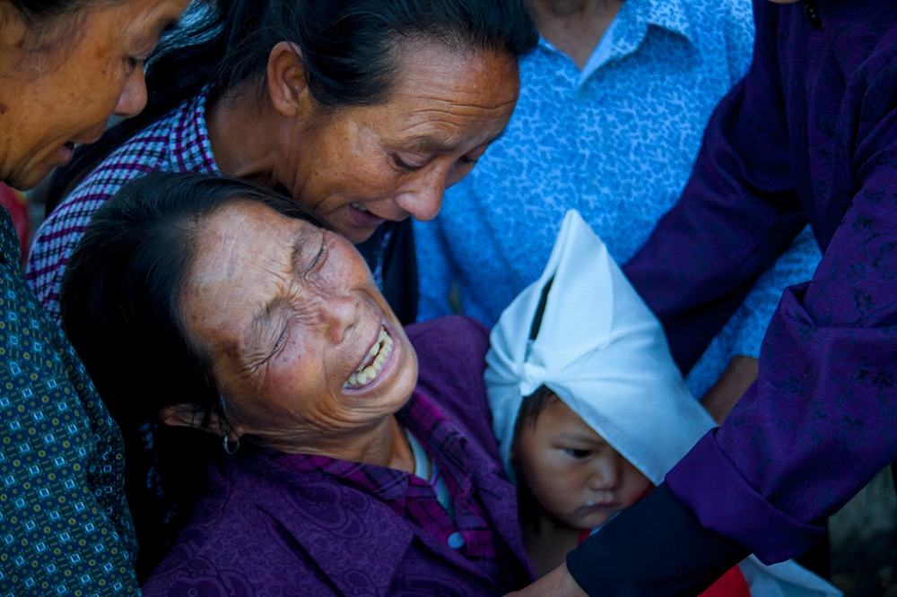 Zhu Huaxiang, cries outside of the family home as friends and relatives try to move her inside and away from the funeral guests, with her husband gone, the care of her grandchildren rests more heavily on her shoulders.