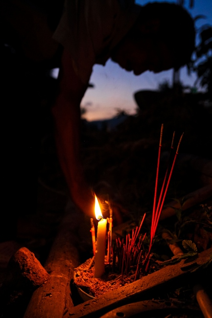 A candle burns at an alter in the early sunlight.