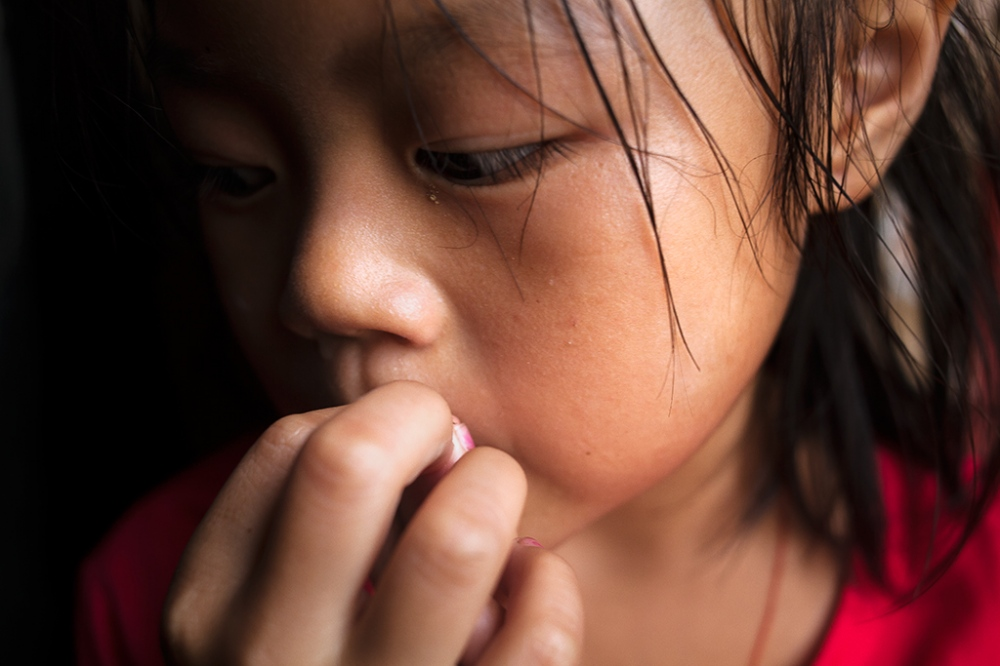 The eldest Huang daughter, Huang Junyan, cries softly to herself in the corner. It is not easy to be a girl in rural China where many families still prefer boys. Women frequently receive bad treatment.