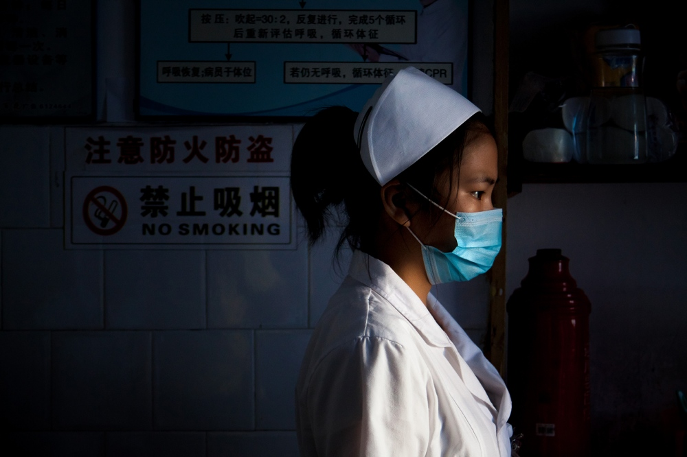 A nurse looks on as Li XiaoWei is treated with antibiotics after an emergency C-section. The cost of these treatments takes a huge toll on the Huang family.